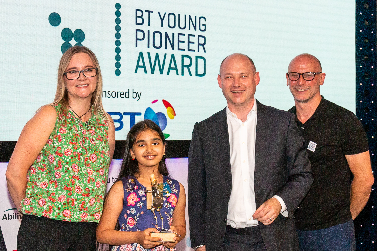 Kate Russell, Mihika Sharma (9), Andy Wales BT and Mark Walker on stage holding the BT Young Pioneer Award