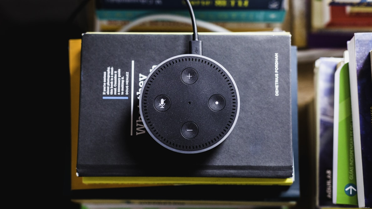 An amazon Echo device on top of a stack of notebooks